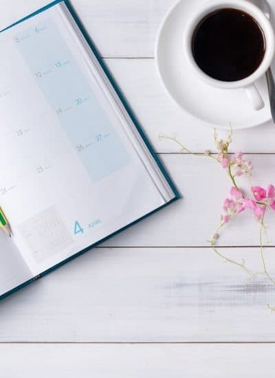 Cup of coffee and calendar for planning $200 a month in dividends