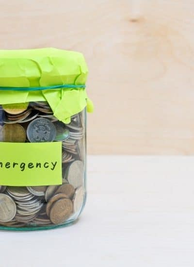Jar of coins with emergency label for setting up a 6 month emergency fund