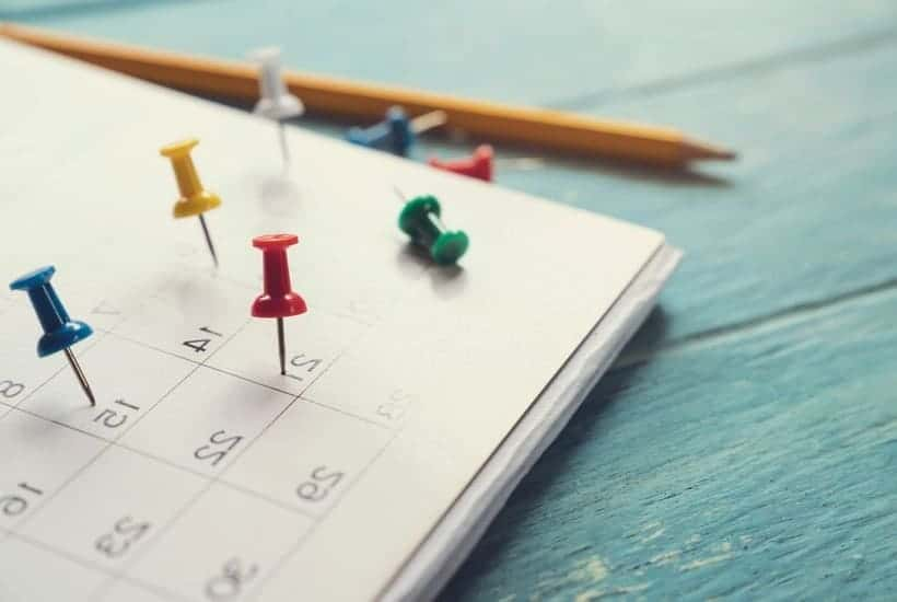 Calendar with pushpins for tracking Dividend Aristocrats payout schedules and patterns