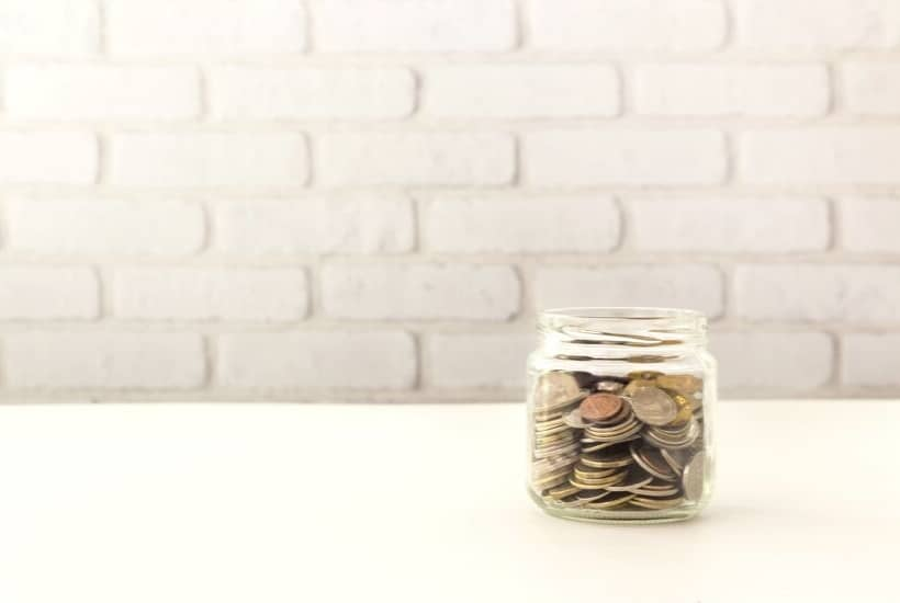 Jar of coins on a white counter while looking at 6 dividend investing mistakes