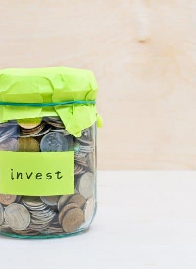 Jar of coins with words invest while deciding between Dividend Stocks vs Index Funds