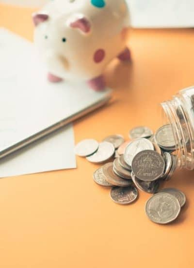 Jar of coins, piggy bank, and paper for setting up the half payment budget method