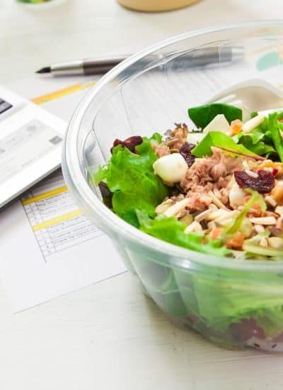 Laptop and bowl of salad while considering the reasons to pack your lunch each day