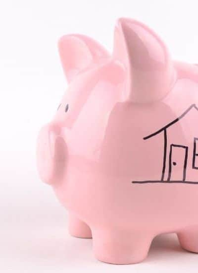 Pink piggy bank with house drawing as a separate account for mortgage payments