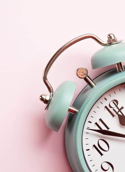 Alarm clock on pink background as a wakeup call about things to consider before starting dividend stock investing