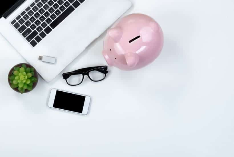Laptop scene with piggy bank while looking into is dividend investing safe?