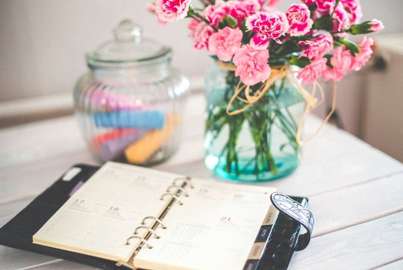 Day planner, vase of flowers, and jar of chalk to help you find time in your hectic schedule