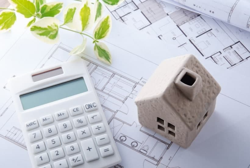 Ceramic house, calculator, and house blueprints while considering skipping escrow