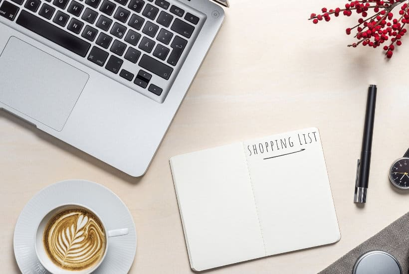 Laptop and grocery shopping list notebook for planning your next trip to the store