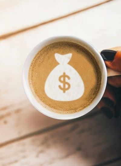 Hand holding a coffee much with money bag swirl before planning a $500 a month in dividends portfolio