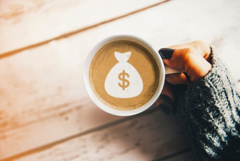 Hand holding a coffee mug with money bag swirl before planning a $500 a month in dividends portfolio