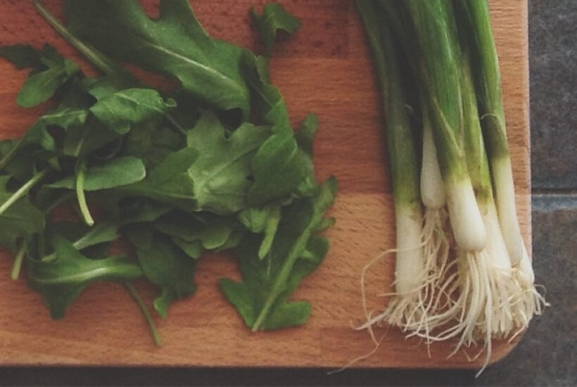 Fresh produce on a cutting board while preparing to store green onions