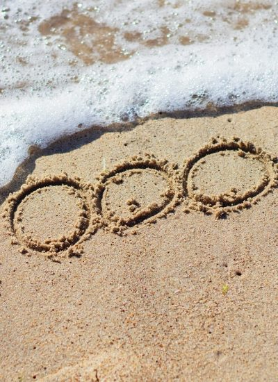 1000! etched into sand with the ocean wave coming in to represent planning a $1000 a month in dividends goal